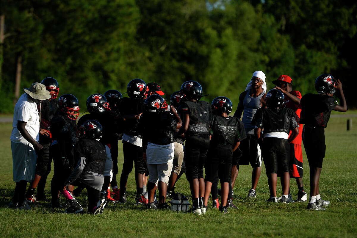 Members of the Beaumont Bulls 11 and 12-year-old football team take a water break during practice on Monday evening. The team kneeled during the national anthem before their game on Saturday. Photo taken Monday 9/12/16 Ryan Pelham/The Enterprise