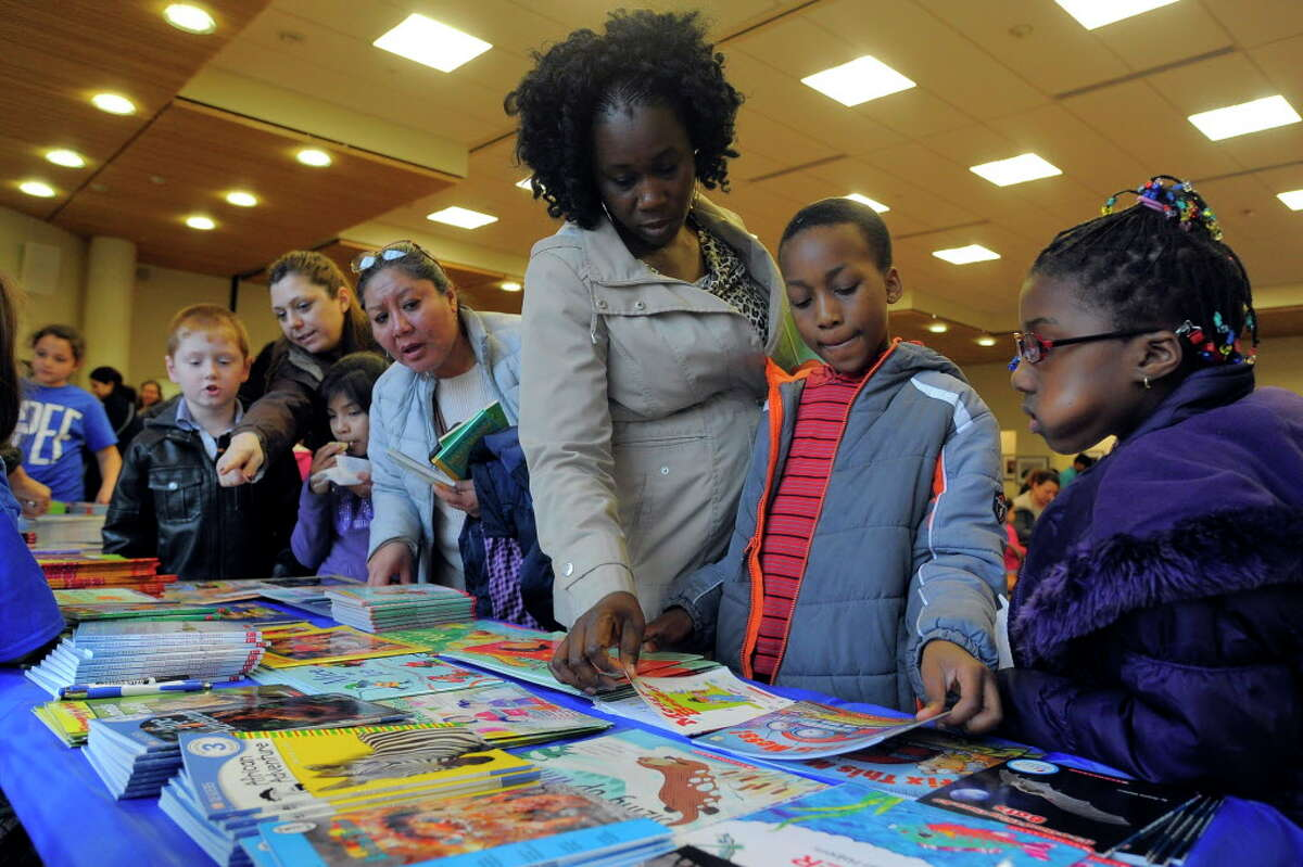 Marcelle Dawson helps her son Alexander pick out a book during the Stamford Public Education Foundation bi-annual Reading is Fundamental Book Give-A-Way at the Ferguson Library. The education foundation is celebrating its 20th anniversary this year.