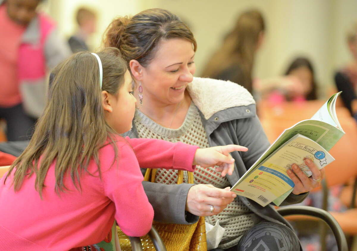 Lina Quintero, of Stamford, reads a book to her daughter Sofia, 6, during the Stamford Public Education Foundation bi-annual Reading is Fundamental Book Give-A-Way at the Ferguson Library. The foundation is celebrating its 20th anniversary this year.