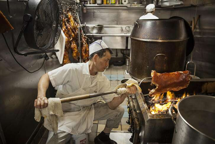 Master B.B.Q. chef Kow Kee Ng hand roasting pig over an open fire Peony Seafood Restaurant in Oakland, California, USA 10 Sep 2016. (Peter DaSilva/Special to The Chronicle)