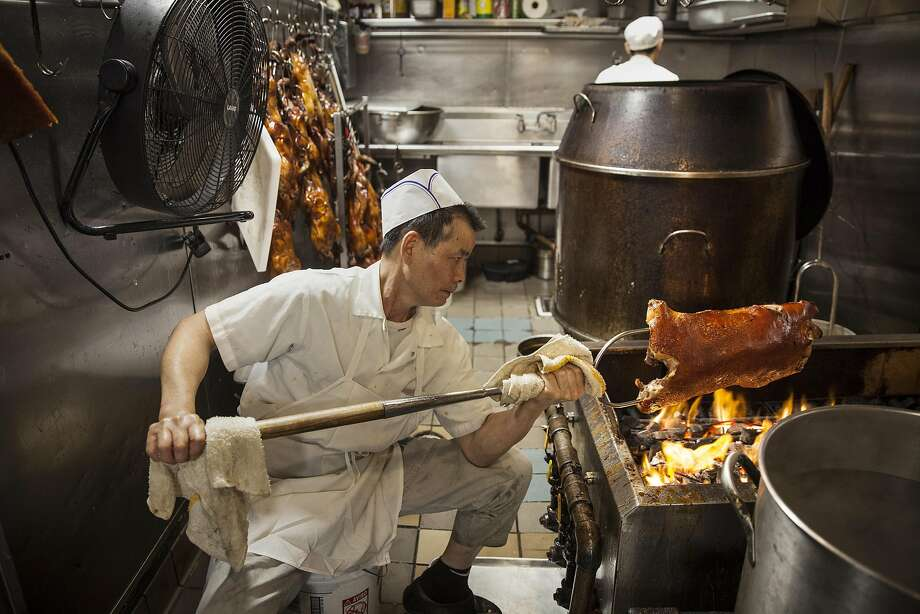 Master B.B.Q. chef Kow Kee Ng hand roasting pig over an open fire Peony Seafood Restaurant in Oakland, California, USA 10 Sep 2016. (Peter DaSilva/Special to The Chronicle) Photo: Peter DaSilva, Special To The Chronicle