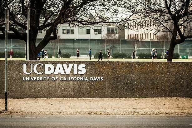 The UC Davis logo with a soccer game and bike riders in the background. University of California at Davis. Davis, California. Taken February 2, 2015.