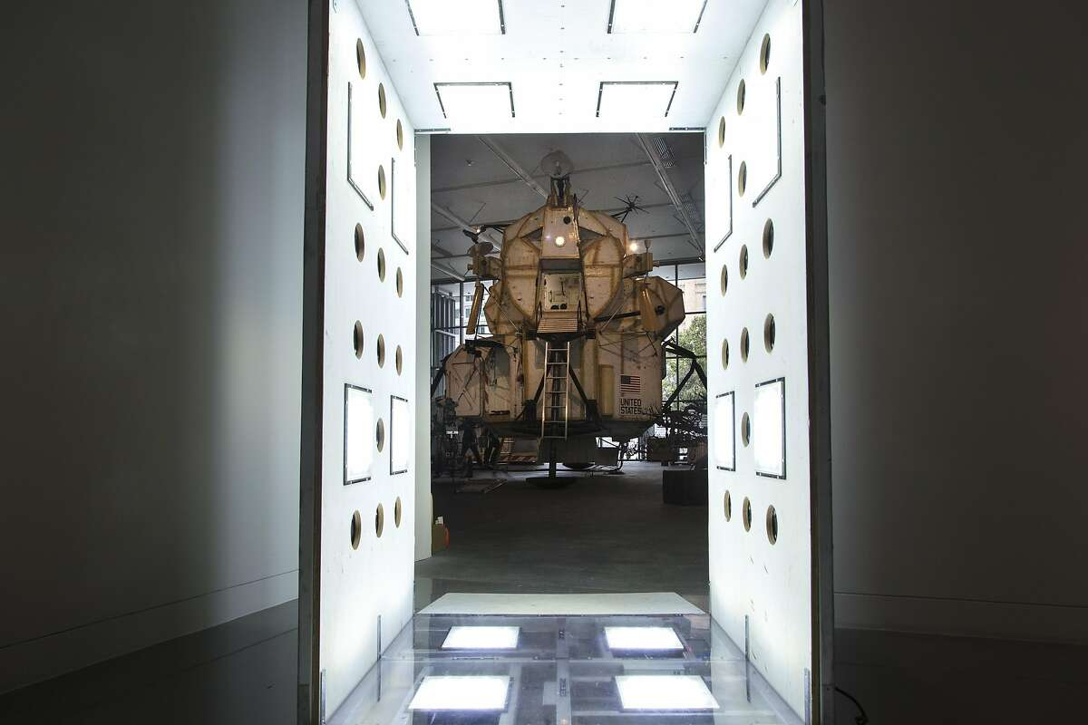 """The 23-foot-tall """"Landing Excursion Module (LEM)"""" (2007-2016) is seen in the background through """"RISCAR: Robert Irwin Scrim Clean Air Room"""" (2012), by Tom Sachs, during """"Space Program: Europa,"""" an exhibition at the Yerba Buena Center for the Arts on Monday, Sept. 12, 2016 in San Francisco, Calif."""
