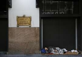 A homeless man sleeps in the entrance to Macy's, before the department store opens, Tuesday, Sept. 6, 2016, in New York. (AP Photo/Mark Lennihan)