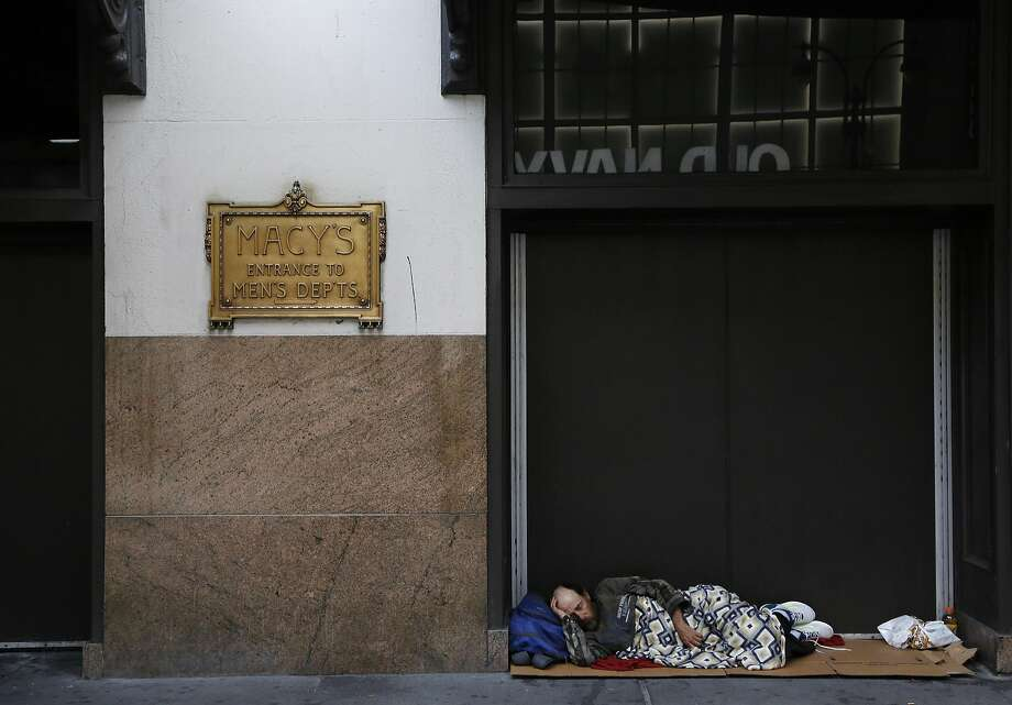 A homeless man sleeps in the entrance to Macy's in New York, before the department store opens and he must find another place to pass the hours. Photo: Mark Lennihan, Associated Press