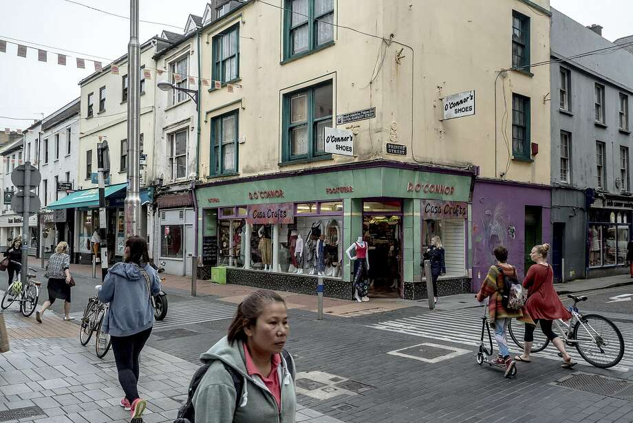 Pedestrians walk and ride the streets of Cork, Ireland, the European headquarters of Apple. The country has been ordered by the European Union's executive commission to collect $14.5 billion in back taxes from the tech giant. Photo: ANDREW TESTA, NYT