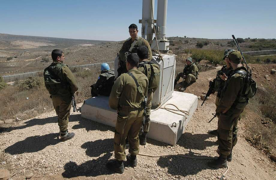 Israeli soldiers and peacekeepers of the United Nations Disengagement Observer Force (UNDOF) (2nd from L) monitor the border with Syria near the village of Majdal Shams in the Israeli-occupied sector of the Golan Heights on September 13, 2016. Israel's military denied a Syrian claim that it had shot down two Israeli military aircraft. The Israeli army earlier said it targeted Syrian army positions after stray fire from its war-torn neighbour hit the Israeli-held zone of the Golan Heights on September 12.  / AFP PHOTO / JALAA MAREYJALAA MAREY/AFP/Getty Images Photo: JALAA MAREY, AFP/Getty Images