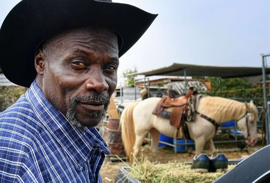 Ivory McCloud poses with his horse, Diamond, at his stable in the backyard of a home in Compton. Photo: Richard Vogel, Associated Press