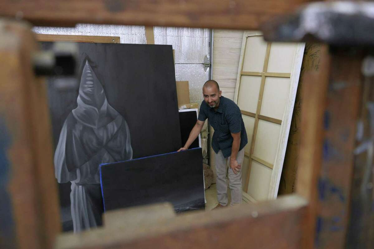 Vincent Valdez sorts through painted panels, in his studio in San Antonio in a photograph from 2016. The artist currently lives in Houston.