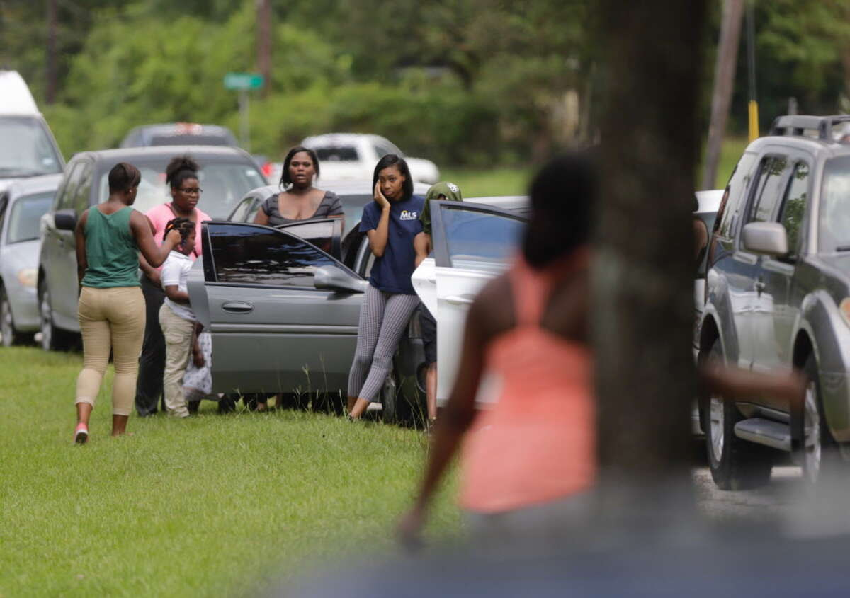People gather at the scene of a fatal shooting at the Uvalde Ranch apartment complex in the 5300 block of South Lake Houston Parkway.