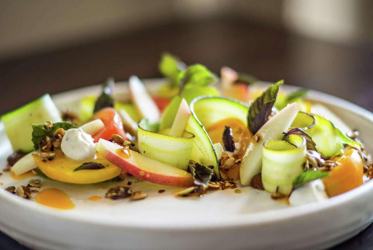 Heirloom Tomato, white peach, charred squash, kefir tzatziki, seeded granola and opal basil at Pax Americana