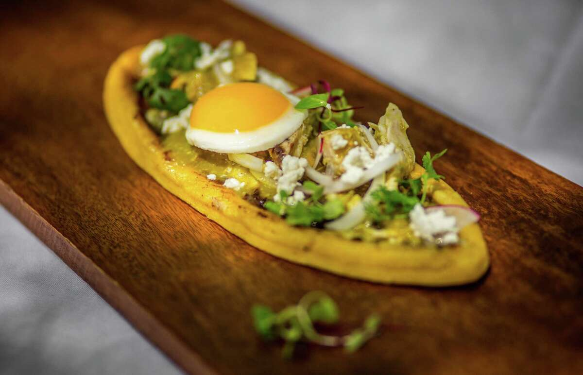 Huarache con Huevos (large sandal-shaped masa cake topped with refried beans, queso fresco, salsa de ajo and chicken served with two eggs sunny-side-up) at Hugo's
