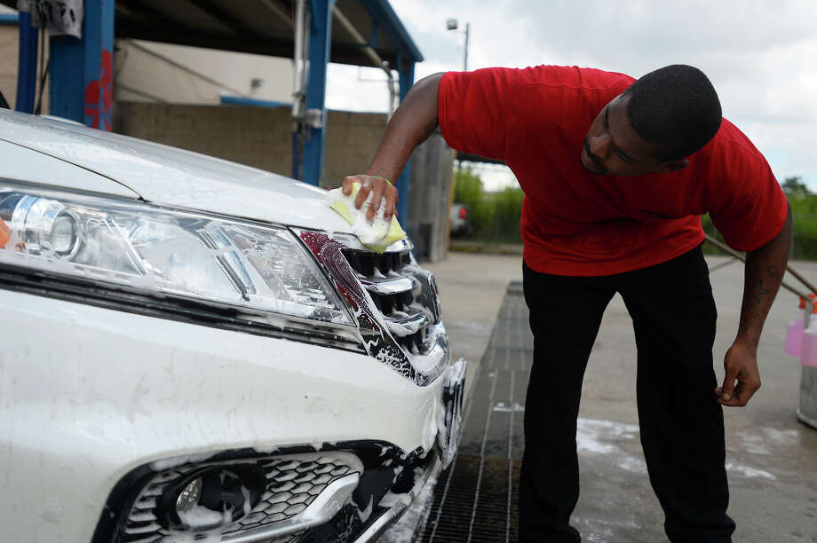 Derek James scrubs lovebugs off a car at The Station Car Wash in Beaumont on Monday.  Photo taken Monday 9/12/16 Ryan Pelham/The Enterprise Photo: Ryan Pelham, Ryan Pelham/The Enterprise / ©2016 The Beaumont Enterprise/Ryan Pelham