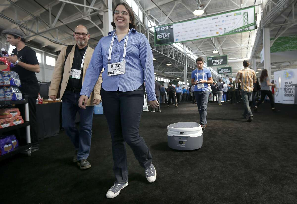 Melonee Wise, CEO of Fetch Robots, walks through Startup Alley with one of her robots in tow at the TechCrunch Disrupt conference in San Francisco, Calif. on Tuesday, Sept. 13, 2016.
