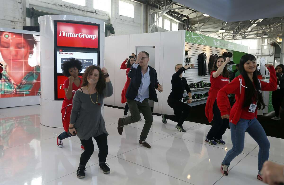 Participants dance at the iTutorGroup display at the TechCrunch Disrupt conference in San Francisco, Calif. on Tuesday, Sept. 13, 2016.