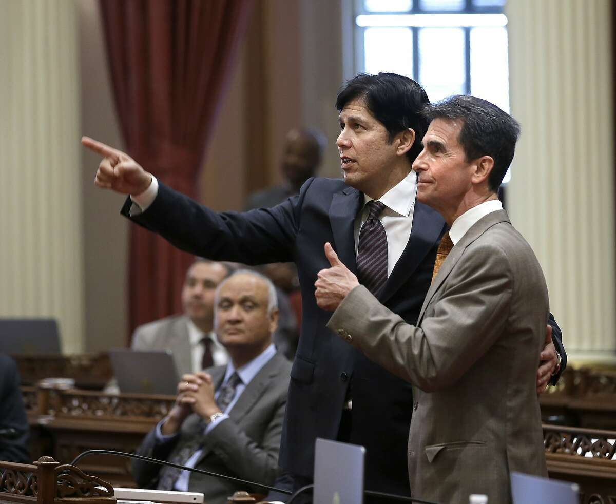 State Sen. Mark Leno, D-San Francisco, right, gives a thumbs up as he and Senate President Pro Tem Kevin de Leon, D-Los Angeles, watch as the votes are posted for a minimum wage bill, Thursday, March 31, 2016, in Sacramento, Calif. The bill, SB3, to gradually raise California's minimum wage to a nation leading $15 an hour by 2022, was approved by both houses of the Legislature and sent to Gov. Jerry Brown. (AP Photo/Rich Pedroncelli)