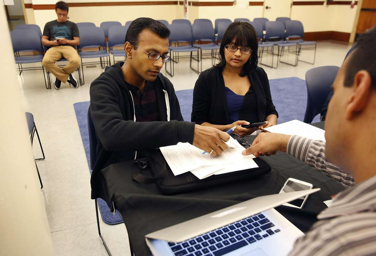 Omar Masry, Senior Administrative Analyst, right, helps Mehul Dhorda, left, and his wife Arpita Patel with registering their short term rental during a public information workshop held by San Francisco's Office of Short-Rent Rentals for vacation-rental hosts to learn about their registration requirement with the city in the Presidio Branch Library June 28, 2016 in San Francisco, Calif.