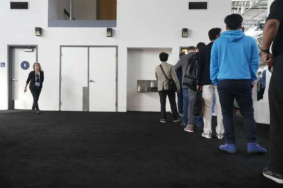Men attending the TechCrunch Disrupt conference stand in a long line to use the restroom while there's no waiting for the women's room (left) in San Francisco, Calif. on Tuesday, Sept. 13, 2016.