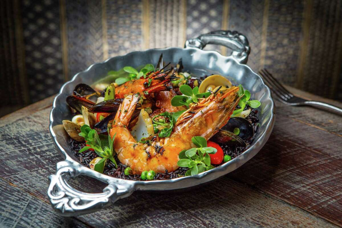 Mariscos con arroz negro with shrimp, clams, mussels, squid, octopus and chorizo with rice cooked in black bean broth at Caracol