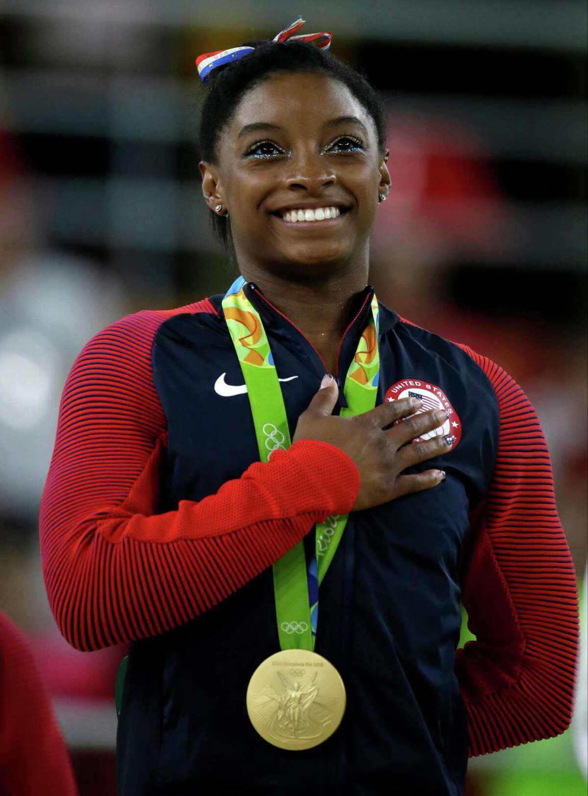 FILE - In this Aug. 16, 2016, file photo, United States' Simone Biles stands during the national anthem after winning the gold medal in the women's floor exercise at the 2016 Summer Olympics in Rio de Janeiro, Brazil. Confidential medical data of gold medal-winning gymnast Simone Biles, seven-time Grand Slam champion Venus Williams and other female U.S. Olympians was hacked from a World Anti-Doping Agency database and posted online Tuesday, Sept. 13, 2016. WADA said the hackers were a