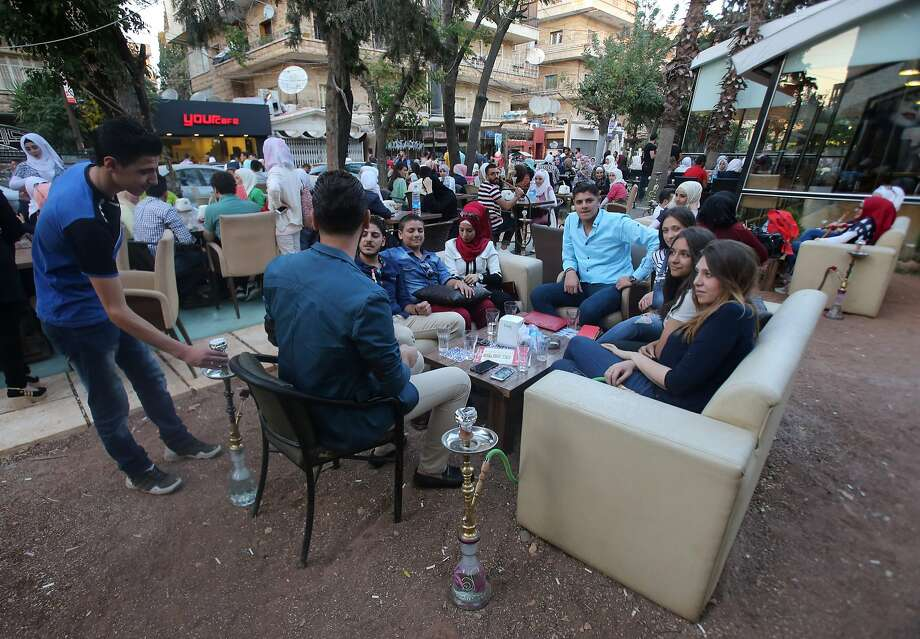Syrian youths sits at a cafe in the government-held area of the northern Syrian city of Aleppo, a day after a fragile ceasefire was brokered. Photo: YOUSSEF KARWASHAN, AFP/Getty Images