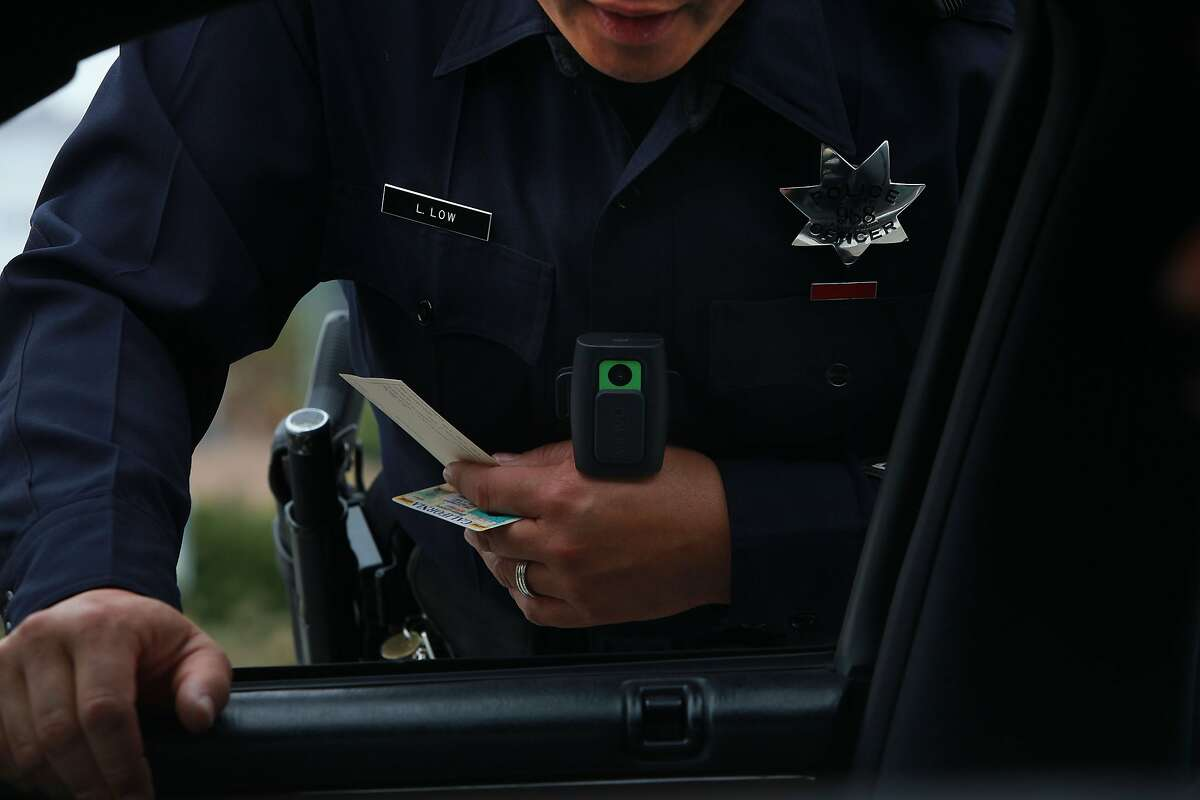 An Oakland officer issues a ticket as he has his new wearable video camera clipped to his uniform (green square) as he stops someone for expired license plates in Oakland, Calif., on Wednesday, September 15, 2010.