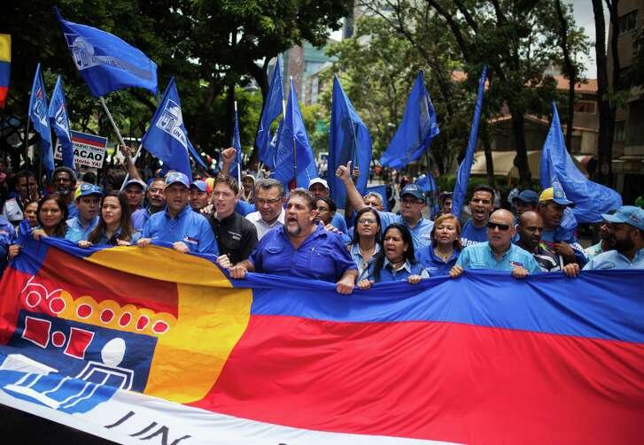 Opposition supporters carry a flag while walking in Chacaito square during a protest against President Nicolas Maduro, not pictured, in Caracas, Venezuela, on Wednesday, Sept. 7, 2016.  (Wil Riera / Bloomberg)