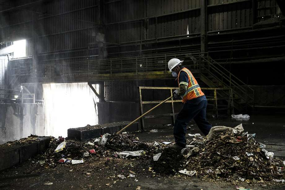 "A worker pushes landfill materials into ""the pit"" at Recology's Transfer Station in San Francisco. Photo: Stephen Lam, Special To The Chronicle"
