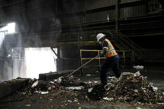 A worker pushes landfill materials into a pit at Recology's Transfer Station in San Francisco, Calif. on Monday, Sept. 12, 2016.