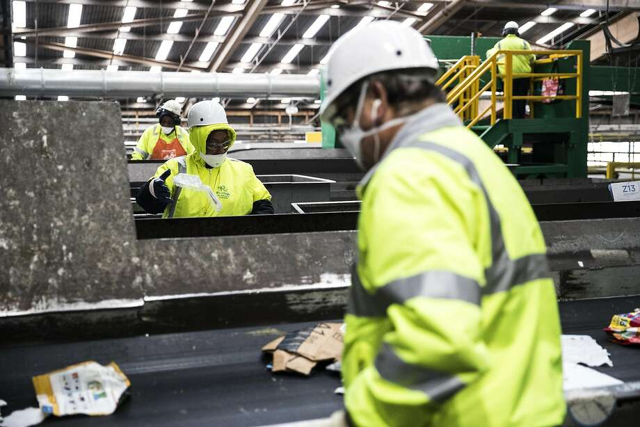 Workers hand-sort recyclables on a conveyer belt during at Recology's Recycle Central at Pier 96. Photo: Stephen Lam, Special To The Chronicle