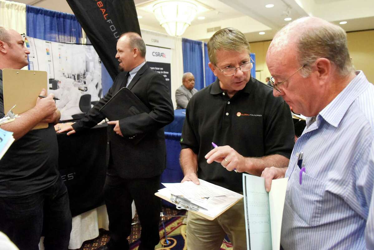 Bill Reed of Global Foundries, second from right, talks with Kevin Guthorn of Ballston Lake during an annual technology and manufacturing job fair on Tuesday, Sept. 13, 2016, at Albany Marriott hotel in Colonie, N.Y. (Cindy Schultz / Times Union)