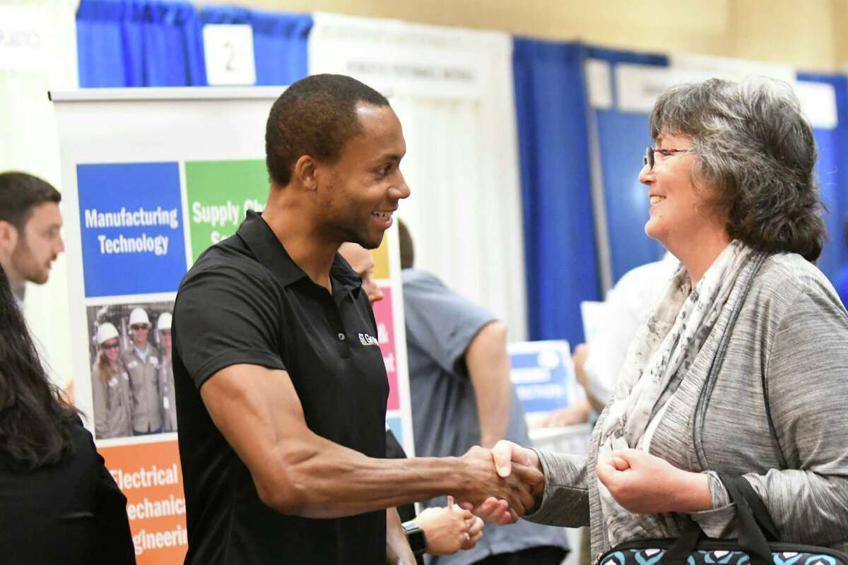 Joseph Zampella of SI Group, center, and Jill Stillman of Queensbury close a conversation with a handshake during an annual technology and manufacturing job fair on Tuesday, Sept. 13, 2016, at Albany Marriott hotel in Colonie, N.Y. (Cindy Schultz / Times Union)