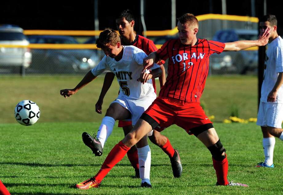 Amity's Thomas Sway, left, kicks the ball away before Foran's Chris Goglia can intercept during boys soccer action in Woodbridge, Conn., on Tuesday Sept. 13, 2016. Photo: Christian Abraham, Hearst Connecticut Media / Connecticut Post