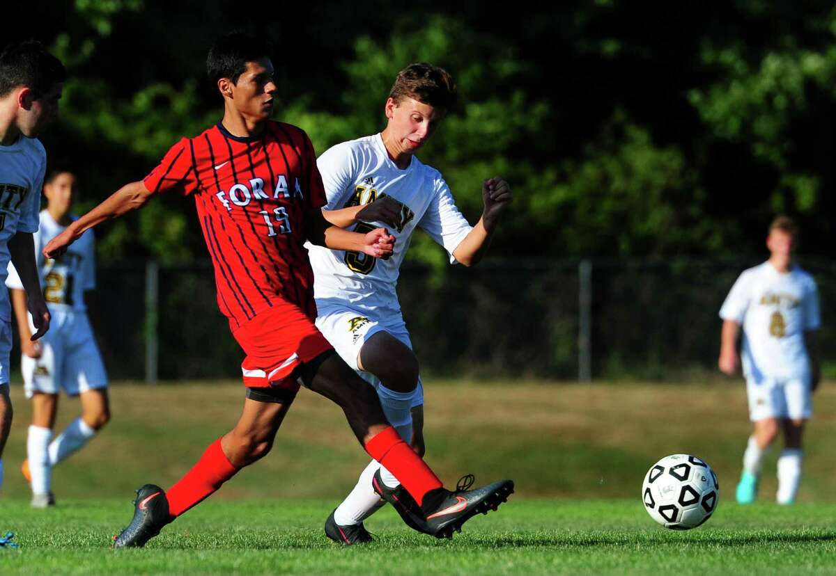 Foran's Glaymer Cardona, left, cuts off Amity's Thomas Sway as they reach the ball during boys soccer action in Woodbridge, Conn., on Tuesday Sept. 13, 2016.