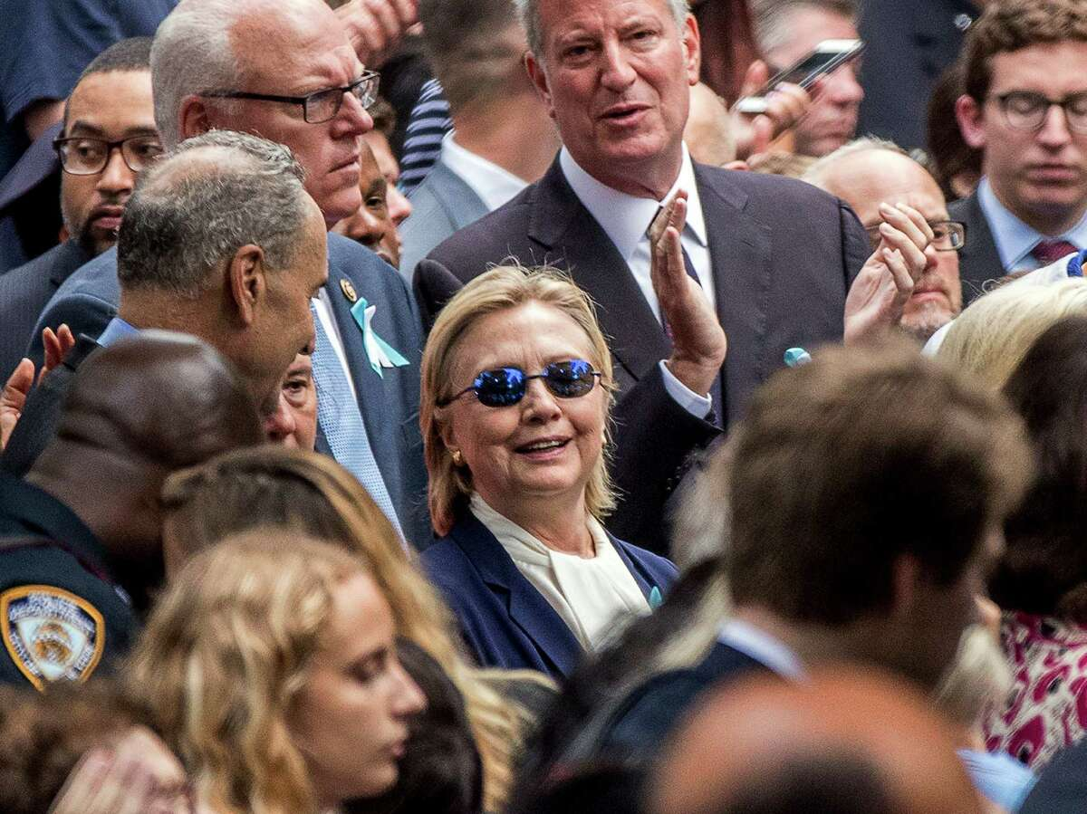 In this Sept. 11, 2016, photo, Democratic presidential candidate Hillary Clinton, center, accompanied by Sen. Chuck Schumer, D-N.Y., left, Rep. Joseph Crowley, D-N.Y., second from left at top, and New York Mayor Bill de Blasio, center top, attends a ceremony at the Sept. 11 memorial, in New York. Clinton will be back on the campaign trail Thursday, after spending several days at home recovering from pneumonia. (AP Photo/Andrew Harnik) ORG XMIT: WX112