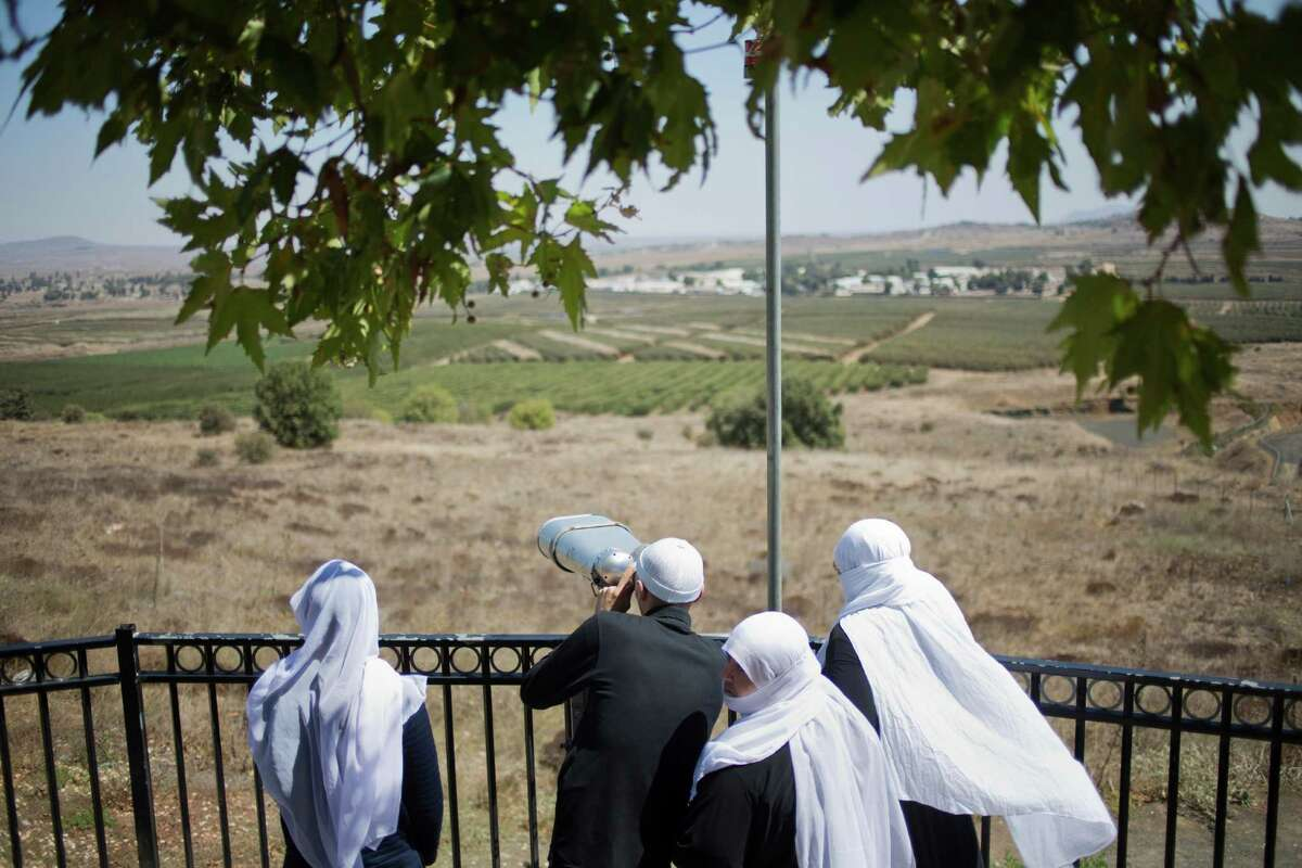 A Druze family, celebrating the Eid al-Adha holiday, look towards Syria's Quneitra province as they visit an observation point in the Israeli-controlled Golan Heights, Tuesday, Sept. 13, 2016. Israel is denying Syrian government claims that its forces shot down a warplane and a drone near the Israeli-controlled part of the Golan Heights. Israeli warplanes have conducted several air raids on Syrian army positions over the past weeks after stray shells hit the Israeli-occupied area. (AP Photo/Ariel Schalit) ORG XMIT: ASC102