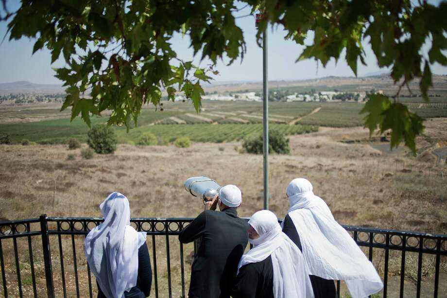 A Druze family, celebrating the Eid al-Adha holiday, look towards Syria's Quneitra province as they visit an observation point in the Israeli-controlled Golan Heights, Tuesday, Sept. 13, 2016. Israel is denying Syrian government claims that its forces shot down a warplane and a drone near the Israeli-controlled part of the Golan Heights. Israeli warplanes have conducted several air raids on Syrian army positions over the past weeks after stray shells hit the Israeli-occupied area. (AP Photo/Ariel Schalit) ORG XMIT: ASC102 Photo: Ariel Schalit / Copyright 2016 The Associated Press. All rights reserved.
