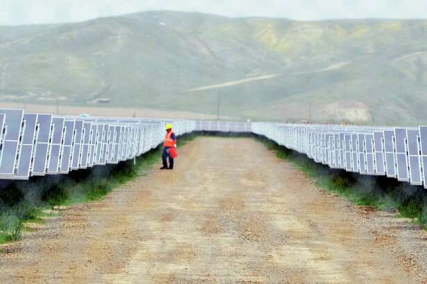 FILE - In this Tuesday, Aug. 3, 2011 file photo, a worker looks over solar panels at the NRG Solar and Eurus Energy America Corp.'s 45-megawatt solar farm in Avenal, Calif. Energy companies are wrapping renewable energy projects and other power-related assets that generate steady cash into new companies they hope attract investors hunting for dividends. (AP Photo/The Sentinel, Apolinar Fonseca, File)