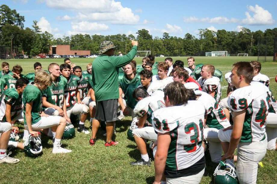 The Woodlands junior varsity football team gathers around coach David Colschen after practice on Tuesday. Photo: Michael Minasi, The Courier