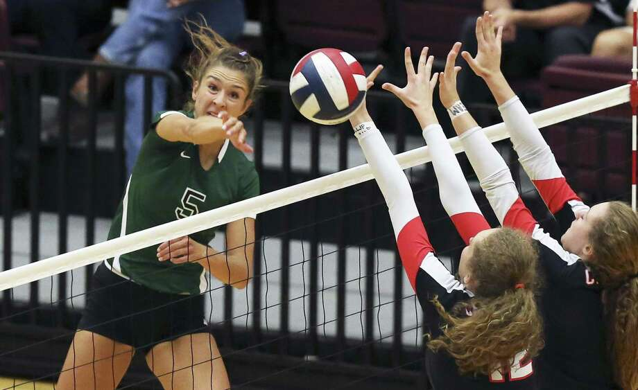Reagan's Camryn Ennis fires a shot past Fiona Garrison (12) and Bailey Retzloff of Churchill at Littleton Gym on Sept. 13, 2016. Photo: Tom Reel /San Antonio Express-News / 2016 SAN ANTONIO EXPRESS-NEWS