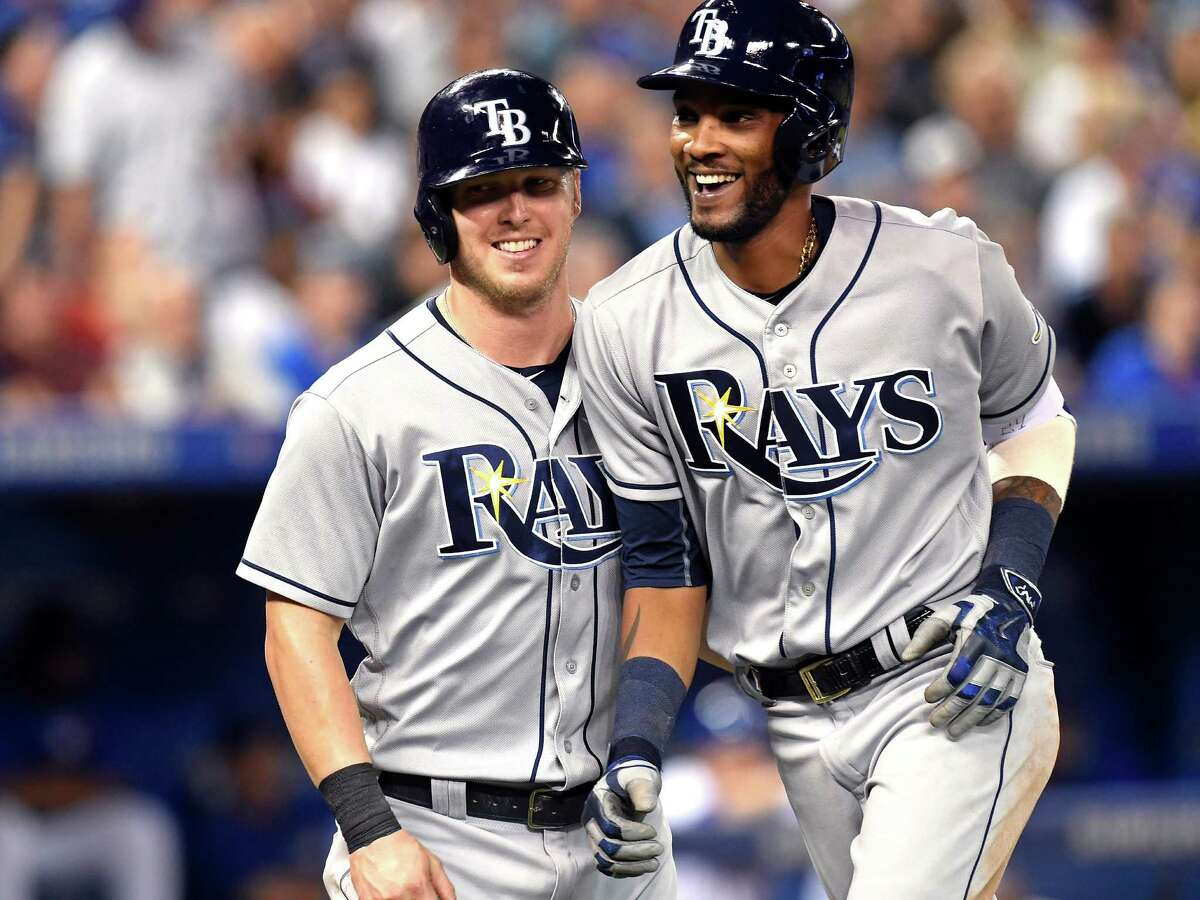Tampa Bay Rays' Corey Dickerson, left, congratulates teammate Alexei Ramirez on his three-run home run against the Toronto Blue Jays during fifth inning American League baseball action in Toronto on Tuesday, Sept. 13, 2016. (Frank Gunn/The Canadian Press via AP) ORG XMIT: FNG505