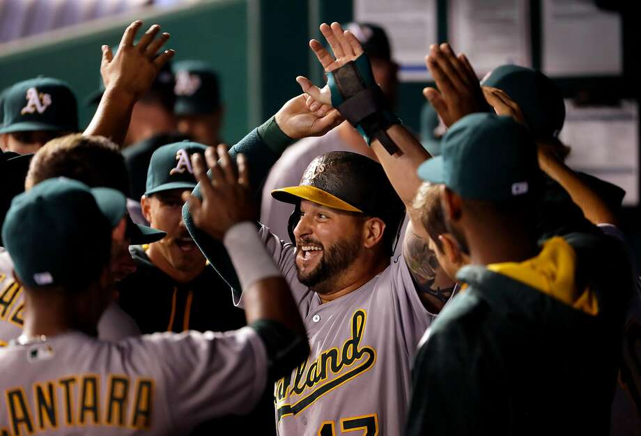 Yonder Alonso is the center of attention in the eighth after he hit a two-run double, then scored on Marcus Semien's single. Photo: Jamie Squire, Getty Images