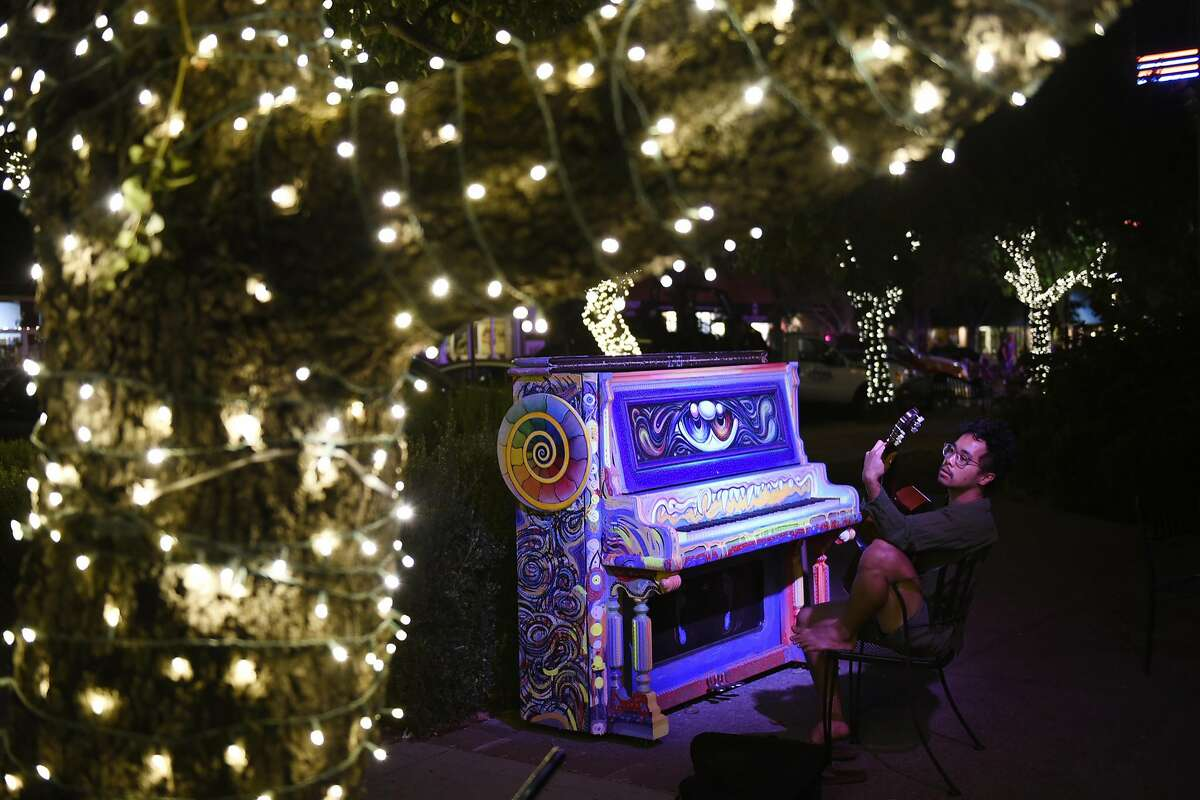 UC Davis student Kawayan Deguzman plays his guitar under lighted trees while sitting in from of an public art piano in Davis, CA Thursday, September 8, 2016.