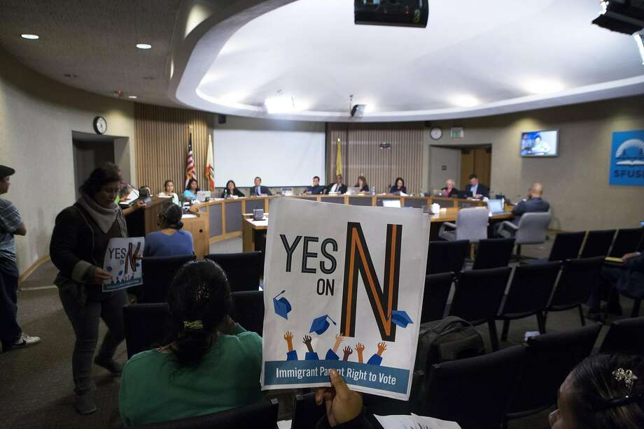 Diana Vasquez (center) holds up a sign as she listens to public comment during an S.F. Board of Education meeting at which the members voted to support Proposition N, which would allow immigrant parents to vote in school board elections. Photo: Santiago Mejia, Special To The Chronicle