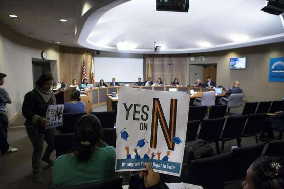 Diana Vasquez, center, holds a sign up in the air, as she listens to public comment, during an SFUSD meeting, on Tuesday, Sept. 13, 2016 in San Francisco, Calif. The school board passed a decision to support Prop N, which, if passed by voters later this year, would authorize S.F. residents, who are not U.S. citizens, but have children who attend S.F. schools, to vote in elections for the Board of Education. Vasquez is a mother of two children who attend S.F. schools.