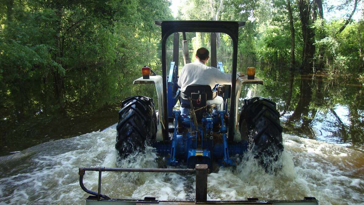 David Lester drives a tractor through a flooded street in Breaux Bridge, La. (Molly Hennessy-Fiske/Los Angeles Times/TNS)
