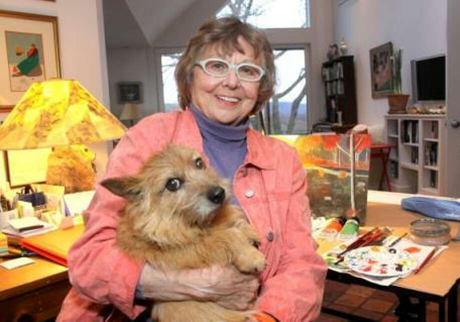 Faith Stewart-Gordon at home in Bridgewater with one her dogs, Little Mac, and the materials she uses to paint colorful renditions of the world around her. Photo: Contributed Photo
