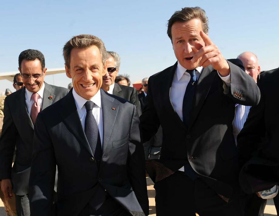 """David Cameron (right) arrives in Benghazi, Libya, in 2011. Britain's military action was based on """"erroneous assumptions,"""" a parliamentary panel said. Photo: Stefan Rousseau, Associated Press"""