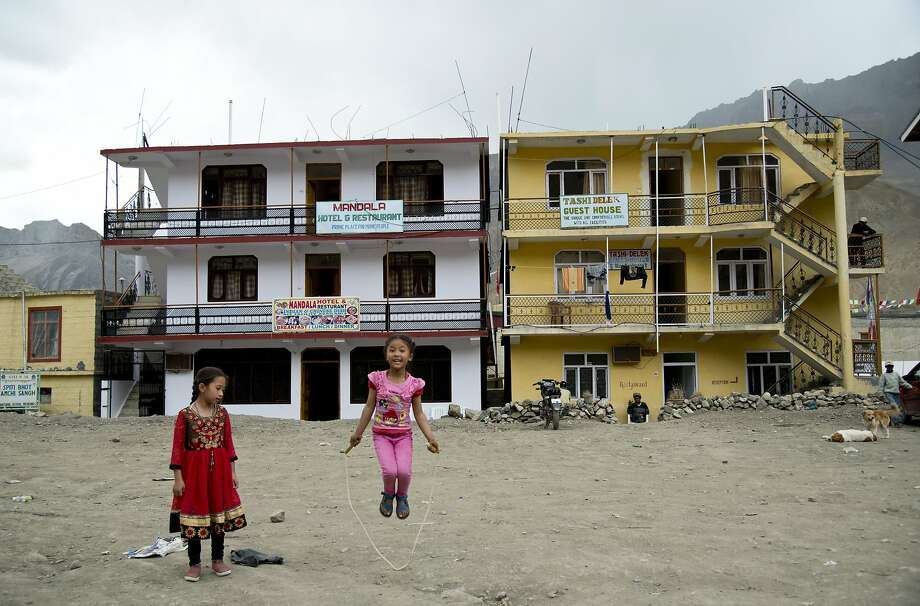 Two girls play in front of newly constructed hotels in the Spiti Valley. For centuries, the region nestled in the Indian Himalayas remained a hidden Buddhist enclave forbidden to outsiders. Photo: Thomas Cytrynowicz, Associated Press
