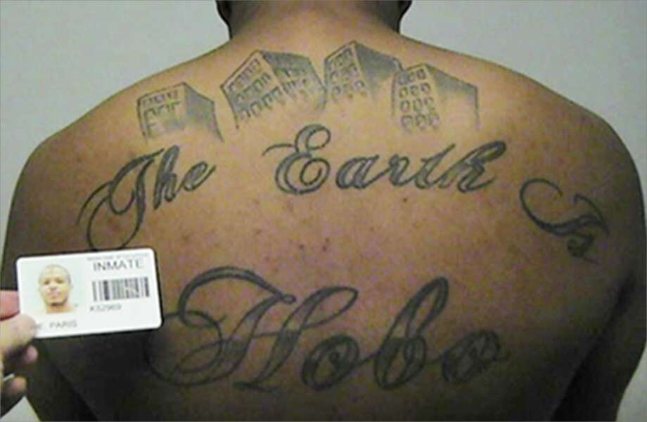"Paris Poe's back tattoo reads ""The Earth Is Our Turf."" He is one of six defendants on trial for racketeering and other charges and being purported leaders of the Hobos, a South Side gang. Photo: Associated Press"